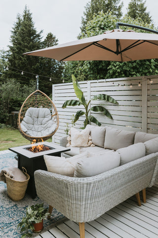 White and minimalist outdoor space with a white wicker couch and outdoor cushions and pillows, a rattan outdoor swing and white baseboards
