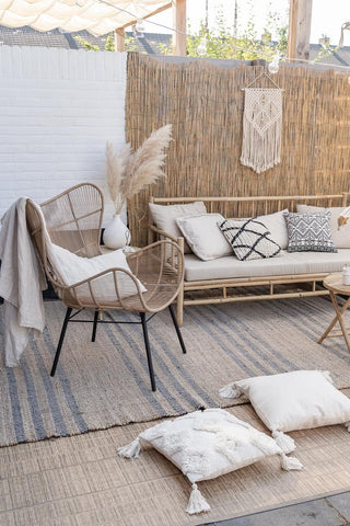Outdoor rug home decor inspiration with rattan outdoor furniture, pampas grass, and outdoor cushions