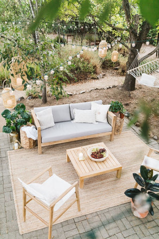 Neutral and earth toned outdoor space with a beige outdoor rug and wood and rattan furniture; boho-chic inspired outdoor home decor