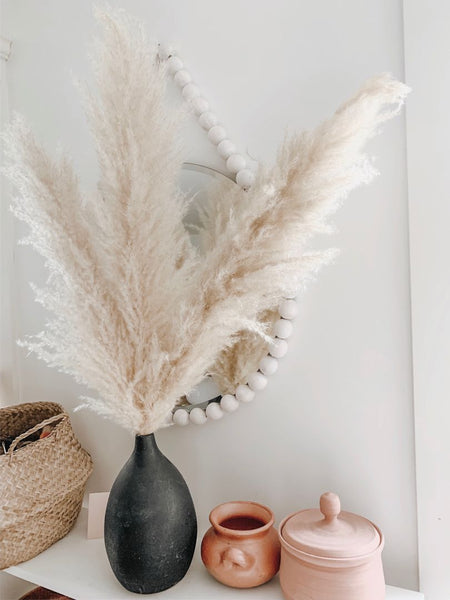 Shelf with dried pampas grass in a vase, minimalist ceramics, and a white, beaded mirror. Boho, minimalist, pampas grass home decor inspiration