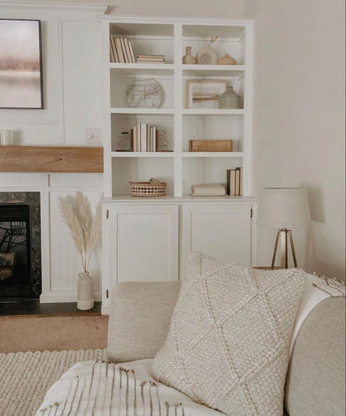 Living room with pampas grass, bunny tails and dried florals. Bookshelf with white and neutral books, ceramics, and baskets. Boho-inspired, minimalist living room. Golden August