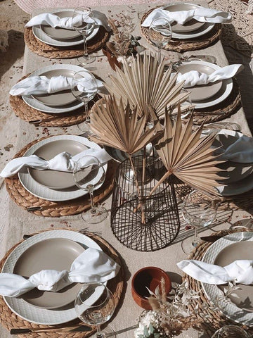 Wicker placemats on a wedding table with dried palm sun centerpieces