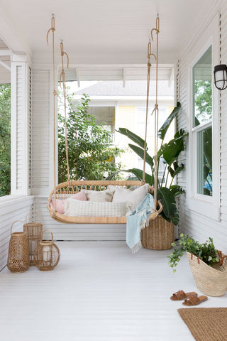 Rattan porch swing with white cushions on an all white, minimalist porch