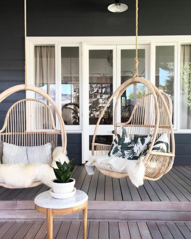 Rattan porch swing on a black patio with white outdoor cushions; minimalist and boho-chic inspired outdoor home decor