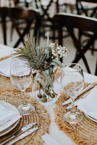 White wedding table with wicker placemats and a succulent centerpiece