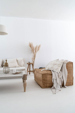 Rattan chair with soft white textiles and dried pampas grass in a bohemian inspired living room
