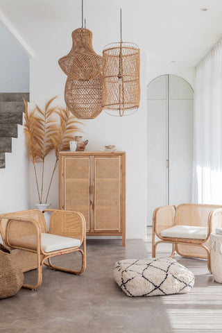 A grouping of rattan light fixtures in a minimalist and bohemian styled living room with rattan chairs and a rattan wardrobe in the background