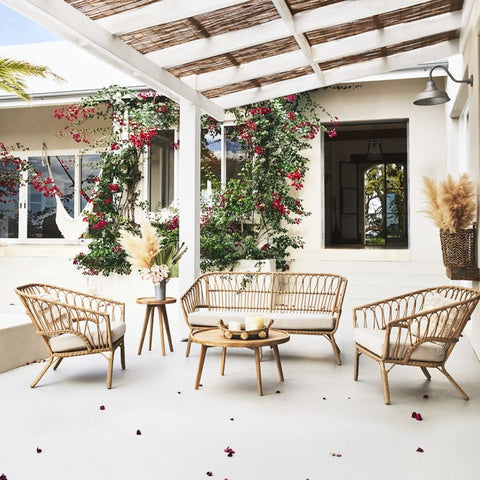 Rattan outdoor furniture set with a rattan couch and two rattan chairs with white cushions surrounded by pampas grass on a patio