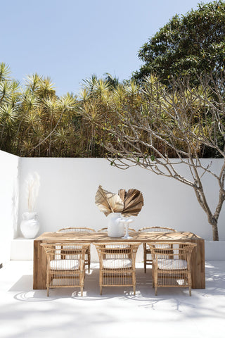 Rattan outdoor furniture featuring a wooden table and rattan table with a palm spear centerpiece on an all white patio