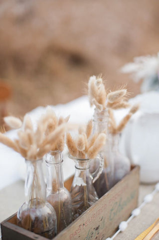 Dried bunny tail centerpieces on a wedding table outside