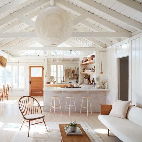 Mix of vintage and modern furniture using natural wood, white textiles, and minimalist home decor accents
