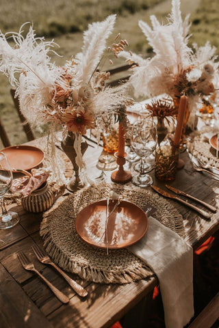 Neutral and earth toned wedding table with wicker and fringe placemats and dried floral and pampas grass bouquet centerpieces
