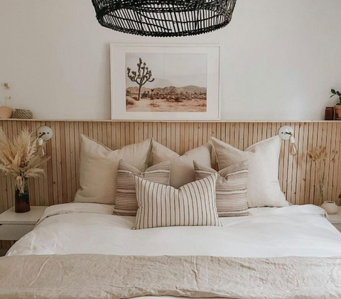 Wood slate headboard on a neutral-toned, minimalist bed with tan and beige throw pillows and a white duvet