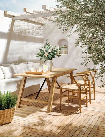 White, minimalist outdoor patio with a wooden table and rattan chairs