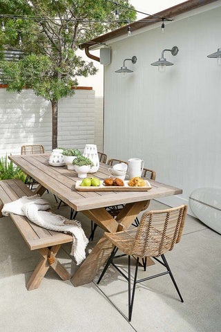 Wooden table and bench on a white patio with a blanket and rattan outdoor furniture accents; boho-chic and minimalist inspired outdoor home decor