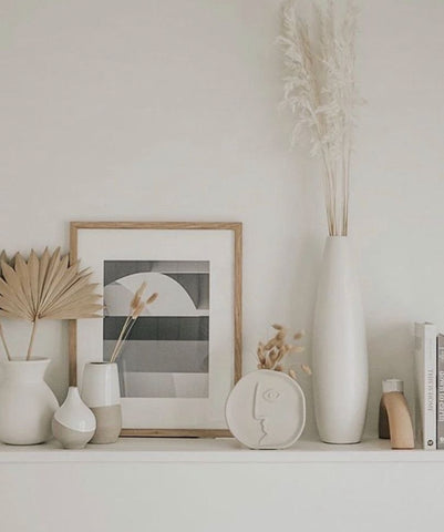 Dried pampas grass and dried palm suns in white ceramic vases on a minimalist and boho-inspired shelf