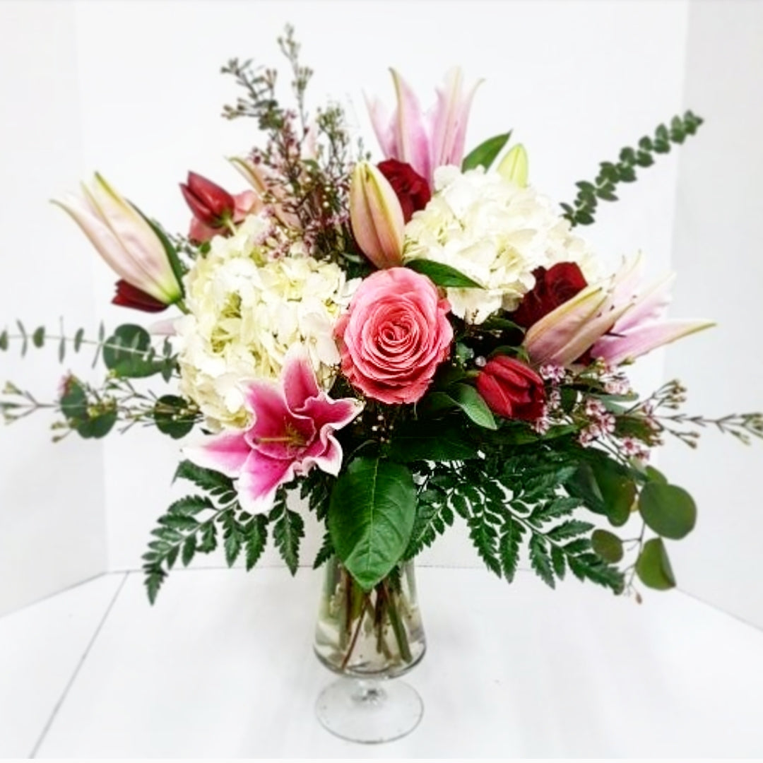 A gorgeous mix of classic romantic blooms including oriental (scented) lilies, hydrangea, roses, tulips, waxflower and mixed foliage spilling out of a footed vase.  Truly a romantic arrangement that will wow and impress your love.