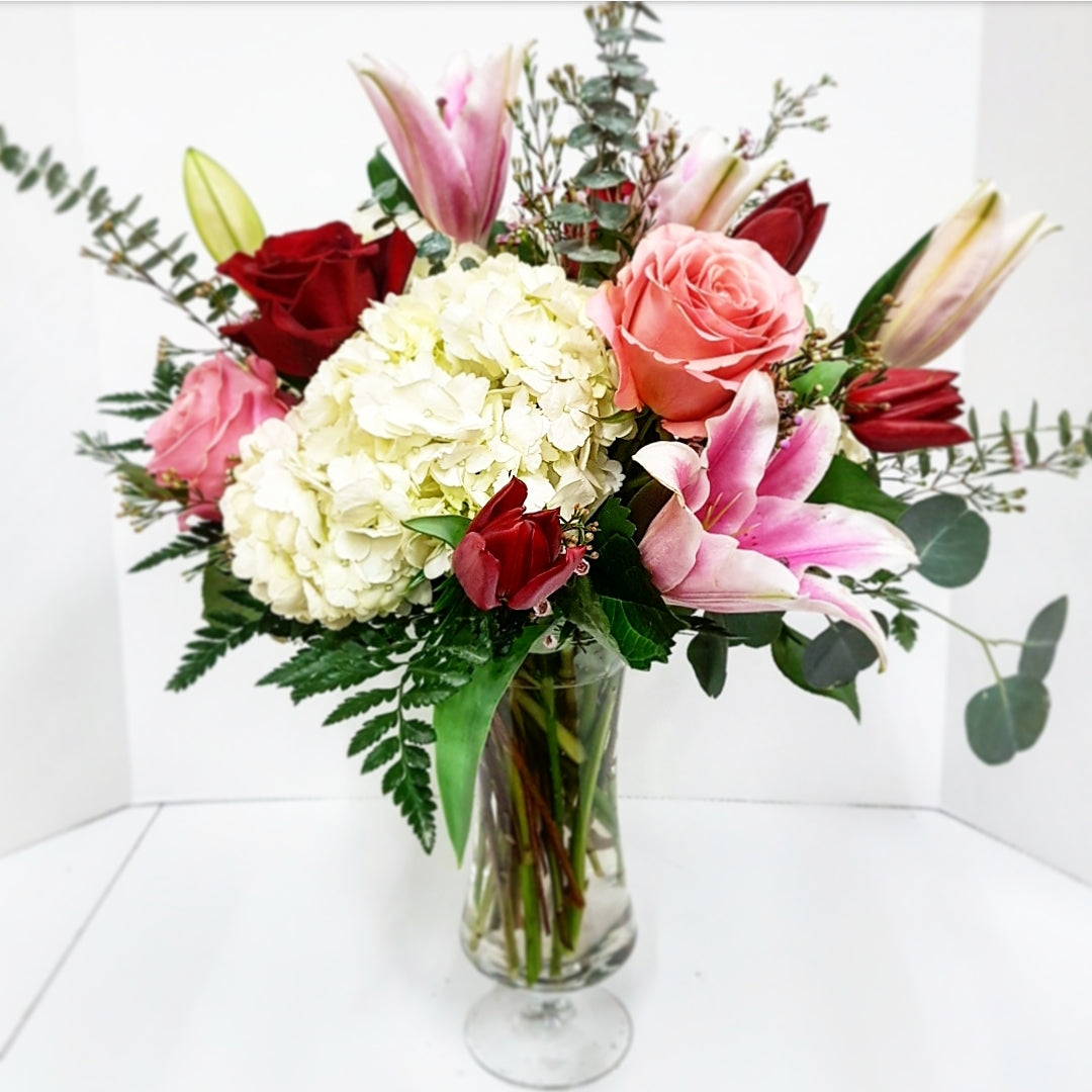 A stunning mix of classic romantic flowers including oriental (scented) lilies, hydrangea, roses, tulips, waxflower and mixed foliage spilling out of a footed vase.  Truly a romantic arrangement that will wow and impress your love.
