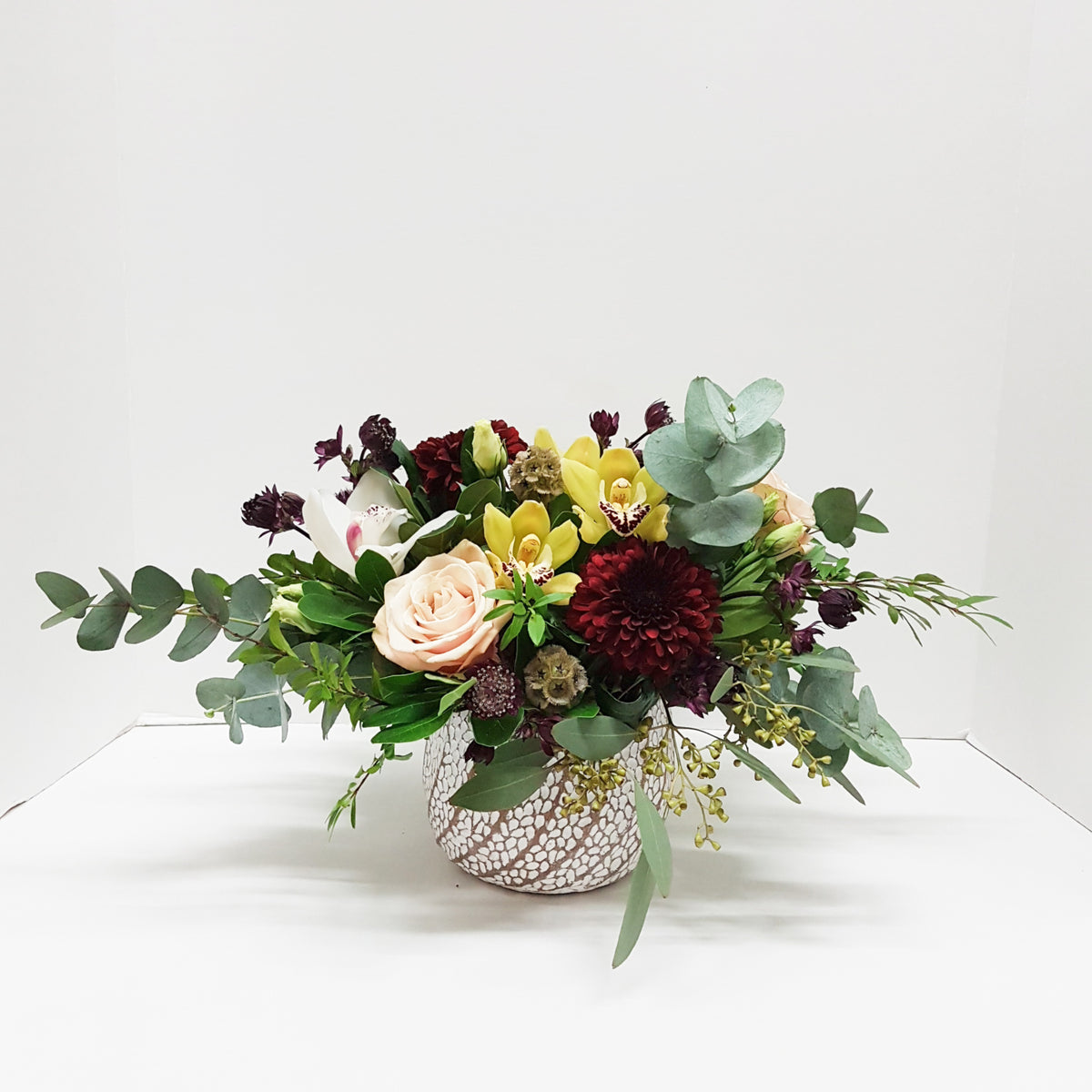 A beautiful mix of fresh flowers including roses, orchid blooms and mixed foliage in a low stylish design.  Color palette in a collection of moody tones.