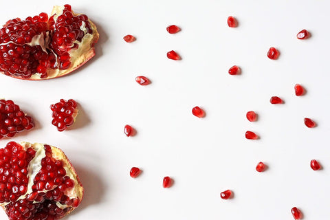 Image of a cut open pomegranate with its sees scattered across the table surface