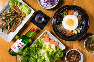 A delicious spread of Korean food including Korean noodles with a bottle of Soju