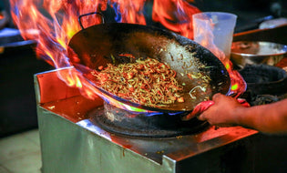 Chinese food being cooked in a wok at a street-side food stand
