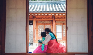 A mother and daughter dressed in identical hanboks sitting in the doorway