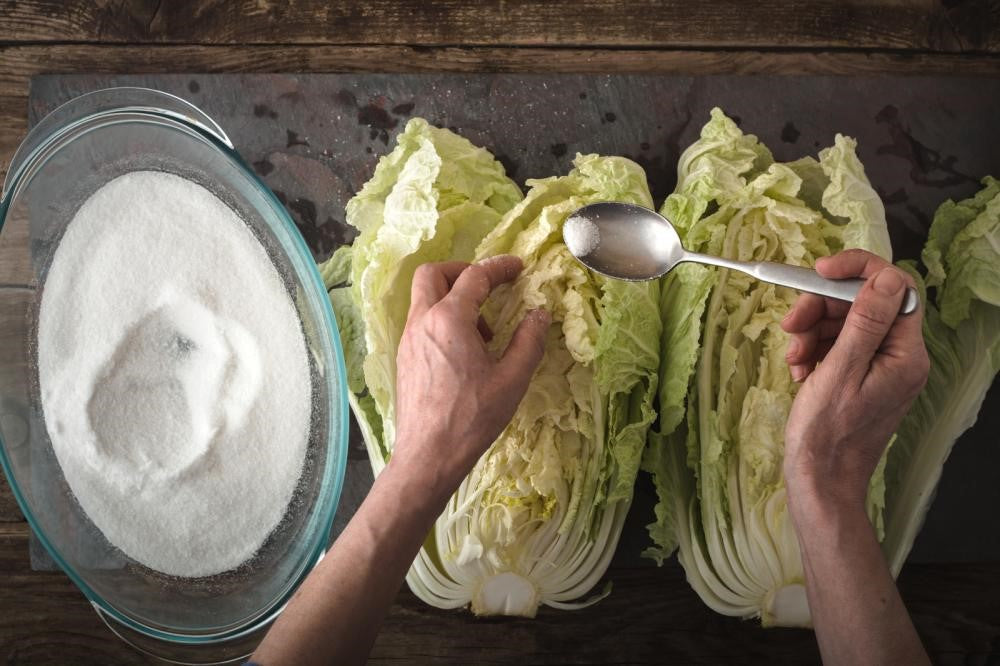 Chinese cabbage kimchi and ingredients on a wooden table