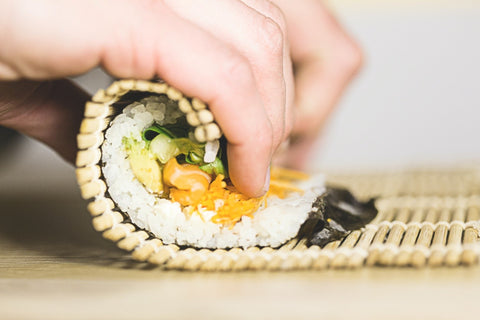 Folding a sushi roll with a bamboo mat