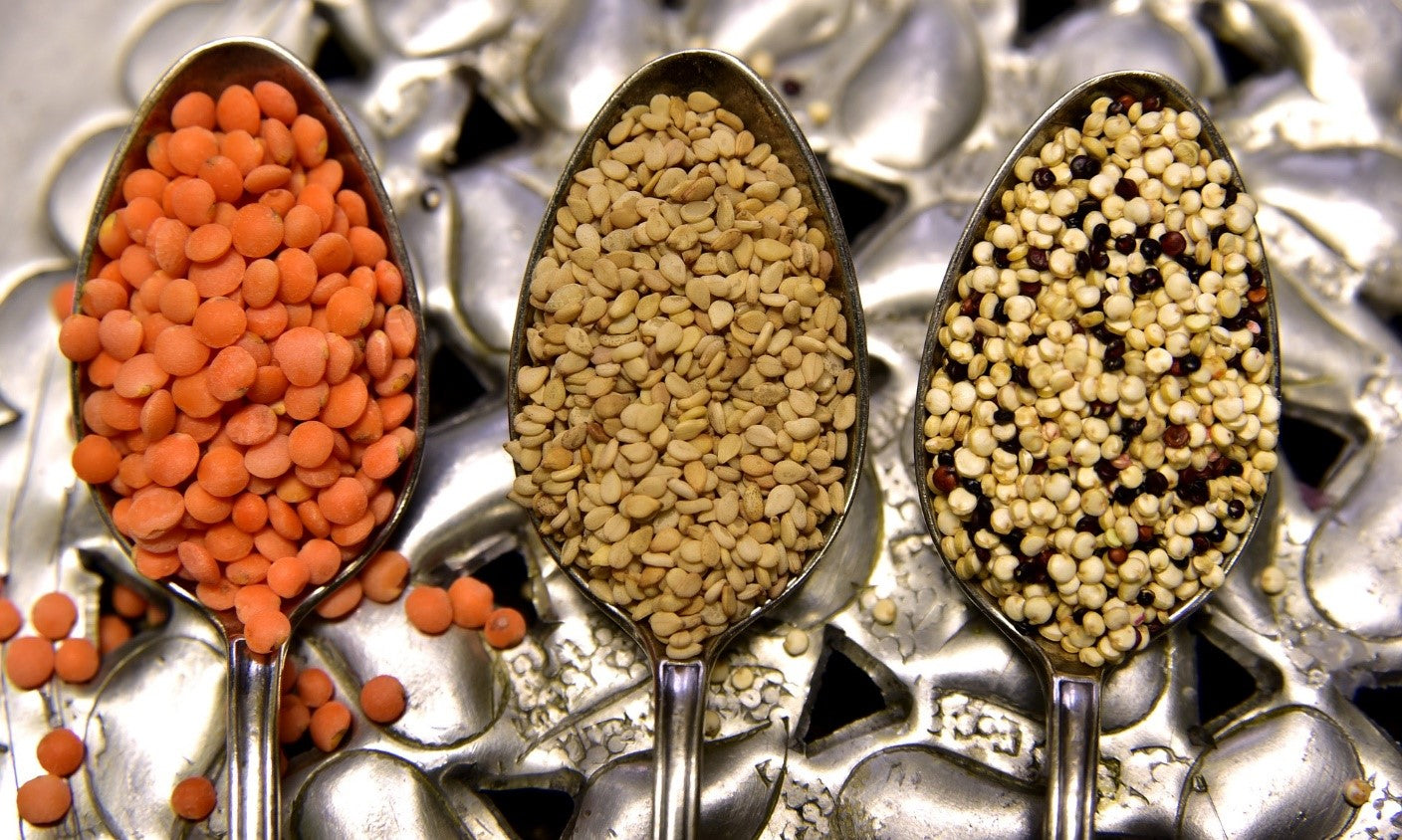 Three different kinds of lentils in spoons.