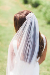 Close up of bride wearing Aster bridal veil with beaded comb by Mauve et Blush outside on her wedding day