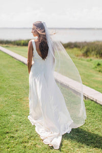 Bride wearing chapel length Aster bridal veil with beaded comb outside that blows in the breeze on her wedding day