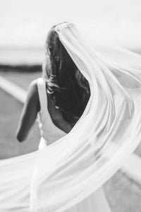 Black and white version of bride wearing Aster bridal veil with beaded comb by Mauve et Blush as it blows outside in the breeze