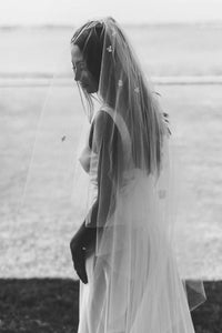 Black and white side portrait of bride wearing Camellia bridal veil by Mauve et Blush outside on her wedding day