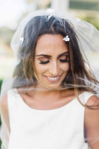 Close up of bride looking down and smiling while wearing Camellia bridal veil with floral beads by Mauve et Blush