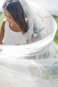 Bride wearing Dahlia wedding veil embroidered with flowers and poetry by Mauve et Blush blowing in breeze outside