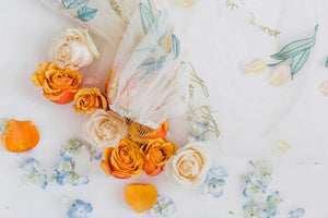 Detail view of Dahlia bridal veil by Mauve et Blush lying on orange and cream roses and blue hydrangea flowers