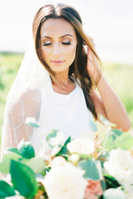 Load image into Gallery viewer, Bride looking down wearing Dahlia bridal veil with embroidered hearts and cupid holding a flower bouquet on her wedding day