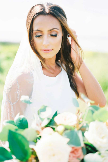 Bride looking down wearing Dahlia bridal veil with embroidered hearts and cupid holding a flower bouquet on her wedding day