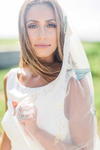 Close up of bride holding her Dahlia embroidered wedding veil by Mauve et Blush looking at camera
