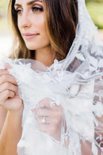Cargar imagen en el visor de la galería, Close up of bride wearing engagement ring and holding Iris wedding veil embroidered with silver thread and floral motif