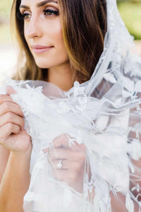 Close up of bride wearing engagement ring and holding Iris wedding veil embroidered with silver thread and floral motif