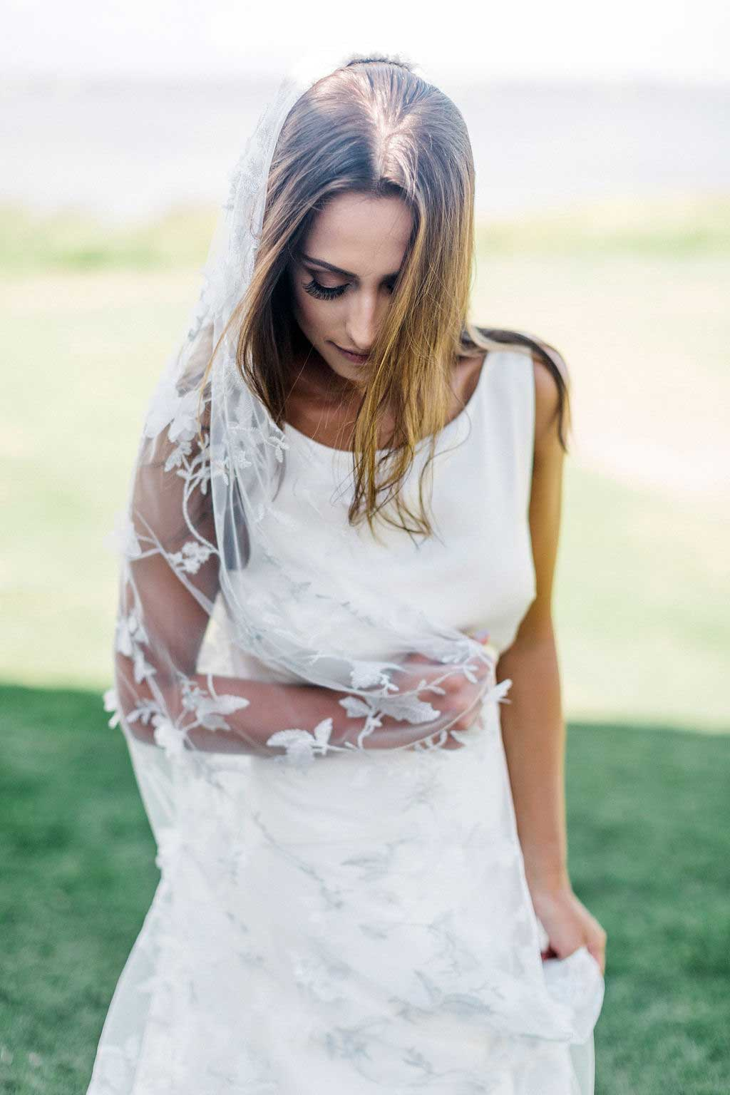 Bride looking down wearing Iris wedding veil by Mauve et Blush embroidered with silver thread and floral motif