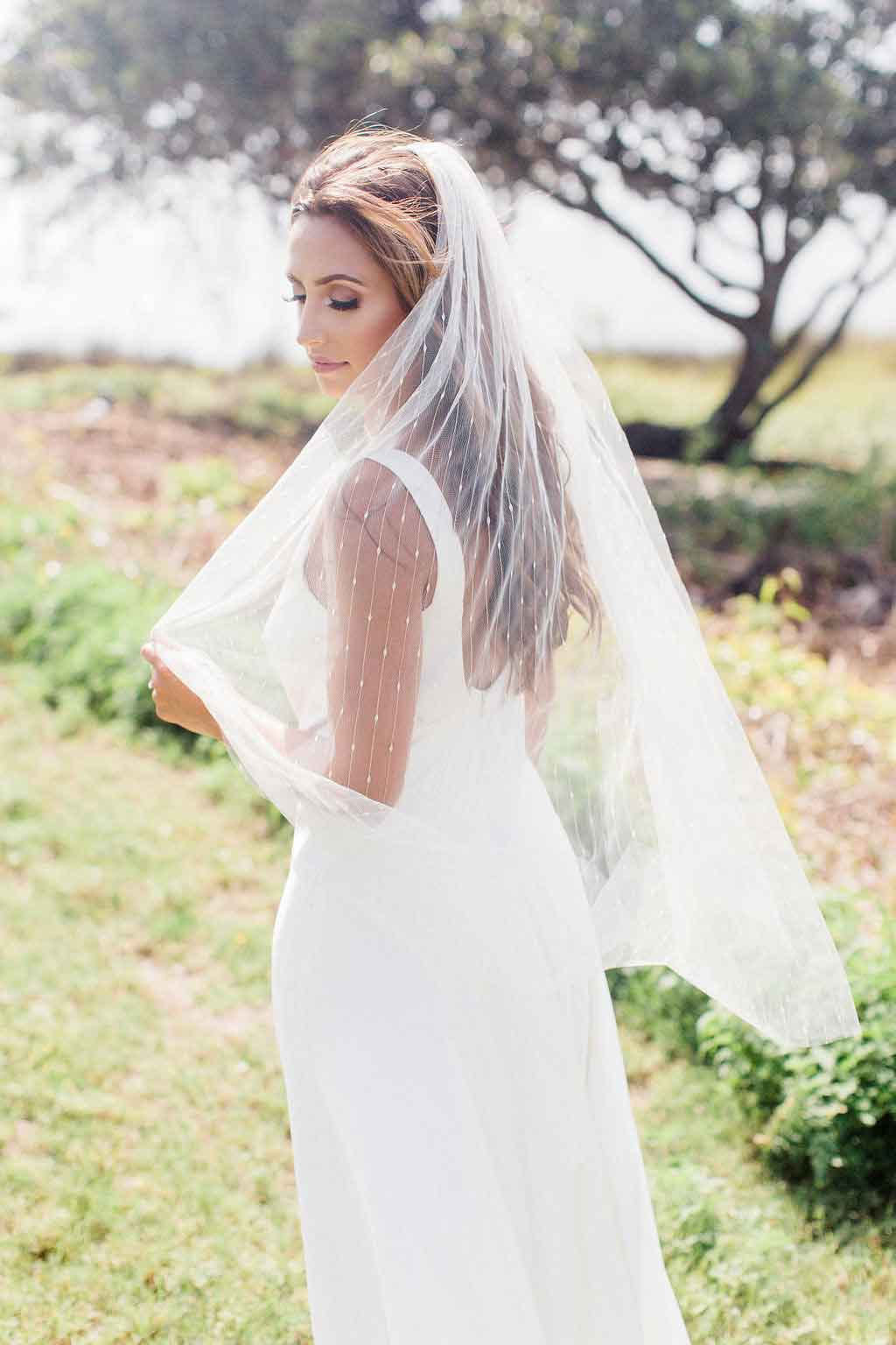 Bride looking over her shoulder wearing fingertip Jasmine bridal veil embroidered with gold thread outside at her wedding