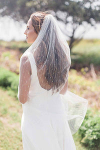 Bride with back turned standing outside wearing Jasmine fingertip bridal veil embroidered with gold stripes
