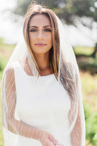 Bride looking at camera wearing fingertip Jasmine bridal veil by Mauve et Blush outside at her wedding