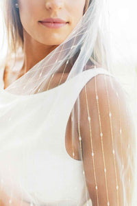 Detail view of bride wearing Jasmine wedding veil embroidered with gold stripes by Mauve et Blush