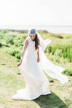 Load image into Gallery viewer, Bride standing outside wearing floral beaded Juliet cap bridal veil by Mauve et Blush as it blows in the breeze