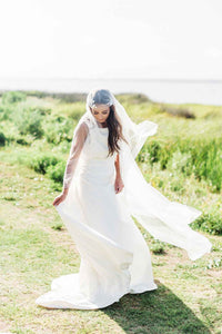 Bride standing outside wearing floral beaded Juliet cap bridal veil by Mauve et Blush as it blows in the breeze