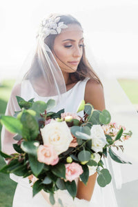 Bride looking over her shoulder outside wearing beaded Juliet cap veil holding a bouquet of white and pink flowers